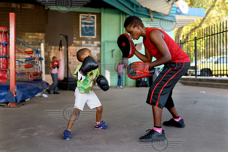 Natalie Baniea trains a young boy during an afternoon session at the George Khosi's Hillbrow Boxing Club. As the club does not have the resources to provide child-size equipment, the youngsters make do with adult gloves.  Hillbrow, in downtown Johannesburg, is the city's most notorious neighbourhood. It is overcrowded, ridden with illegal squats and suffers from high levels of crime much of which is related the thriving illicit drug trade. Against this backdrop, George Khosi's story is not atypical. A childhood spent on the streets, where he survived by committing petty crime and hustling, led to imprisonment at the age of 16. Because he was big and looked older than his age this incarceration was in an adult institution. Here he began to fight since, as he says 'they wanted to make me a woman and I didn't want to be a woman.' When he got out, he took up boxing in earnest. His prospects as a professional boxer looked bright until he was shot and left for dead during a burglary. He lost his right eye and now walks with a limp. His boxing career seemed over but George picked up his gloves again, this time to teach Hillbrow's youngsters. His gym became a place of hope and discipline for local youth, keeping them of the streets and even producing some national champions.