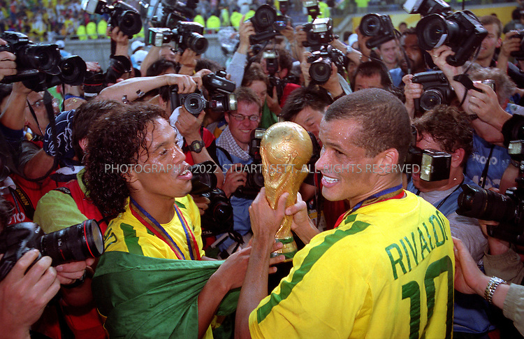 6/30/2002--Yokohama, Japan..Ronaldinho (left) and Rivaldo (right) kiss the World Cup. Brazil beat Germany 2-0...All photographs ©2003 Stuart Isett.All rights reserved.This image may not be reproduced without expressed written permission from Stuart Isett.