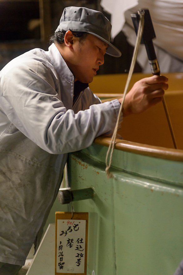 "A brewery worker checking the progress of fermenting sake. Tsuji Honten Sake, Katsuyama town, Okayama Prefecture, Japan, February 1, 2014. Tsuji Honten was founded in 1804 and has been at the cultural centre of the town of Katsuyama for over two centuries. 34-year-old Tsuji Soichiro is the 7th generation brewery owner. His elder sister, Tsuji Maiko, is the ""toji"" master brewer."