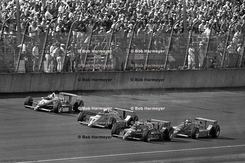 Bobby Rahal (#3) leads a group of cars in his Budweiser-sponsored Truesports March 86C Cosworth during a 1986 CART IndyCar race at Michigan International Speedway near Brooklyn, Michigan.