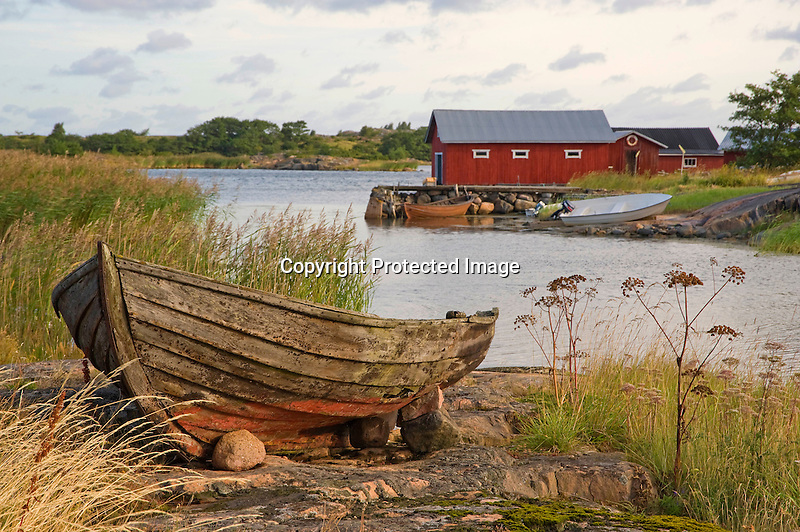 Old Weathered Wooden Boat Resting on the Shore in a Quiet Cove