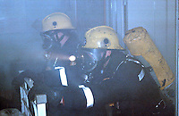 Firefighters in breathing apparatus are searching through a hospital on fire for trapped or patients confined to bed. They have found a patient and have to remove him by pushing the bed out of the ward which is on fire.The fire is blazing out of control through the roof, and the firefighters are working in  temperatures in excess of 2000 degrees centigrade.  On their tunics are right angled intrinsically safe torches. There are also an A.D.S.U., an automatic distress signialling unit, which is part of their B.A. sets. This unit emits a very loud whistle should the firefighters remain motionless for a short period. Therefore, if they are trapped the unit will sound and will allow other firefighters to locate them...© SHOUT. THIS PICTURE MUST ONLY BE USED TO ILLUSTRATE THE EMERGENCY SERVICES IN A POSITIVE MANNER. CONTACT JOHN CALLAN. Exact date unknown.john@shoutpictures.com.www.shoutpictures.com....