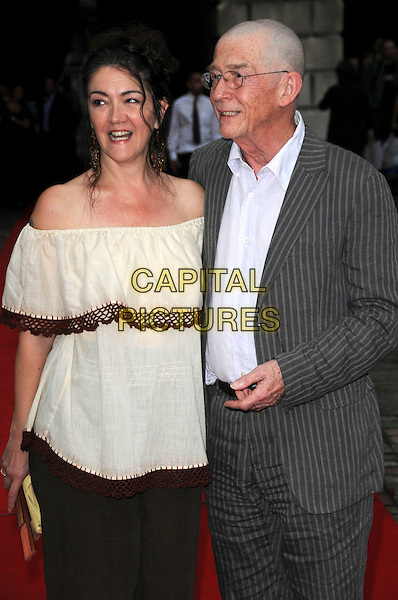 "ANWEN REES MEYERS & JOHN HURT.The ""Hellboy II: The Golden Army "" FilmFour Summer Screen Opening Gala, Somerset House, London, England..July 31st 2008.2 hell boy screening premiere half length married husband wife glasses shaved head grey gray pinstripe suit jacket cream white off the shoulder top .CAP/CAS.©Bob Cass/Capital Pictures."