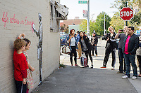 """Street art enthusiasts flock to the Woodside neighborhood of Queens in New York on Monday, October 14, 2013 to see the fourteenth installment of Banksy's graffiti art, """"What we do in life echoes in Eternity"""". The elusive street artist is creating works around the city each day during the month of October accompanied by a satirical recorded message which you can hear by calling the number 1-800-656-4271 followed by  # and the number of artwork.  (© Frances M. Roberts)"""