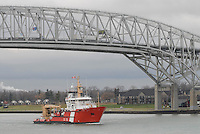 Canadian Coast Guard ice breaker Samuel Risley sails north on the St. Clair River enroute to Lake Huron, past the Blue Water Bridges and The Great Storm of 1913 plaque at the Water Treatment Plant lookout.