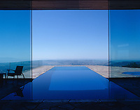 The indoor/outdoor lap pool with sliding glass panels over it allows for swimming whatever the weather with an amazing view over the surrounding landscape
