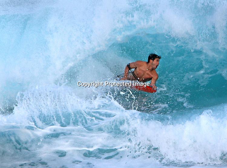 Surfers and beach goers enjoy the high waves at Sandy Beach in Honolulu, HI.