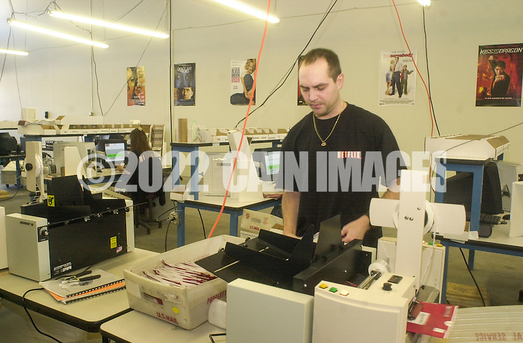 Employees fulfill DVD orders at the new Phoenixville, Pennsylvania distribution center, Wednesday, February 12, 2003, in Phoenixville, Pennsylvania. Netflix plans to open one to two facilities per month for the remainder of 2003 as part of its ongoing strategy to provide one-day movie delivery to its members. By year-end 2003, Netflix expects that it will be able to reach more than 70 percent of its subscribers with generally next-day service. (Photo by William Thomas Cain)