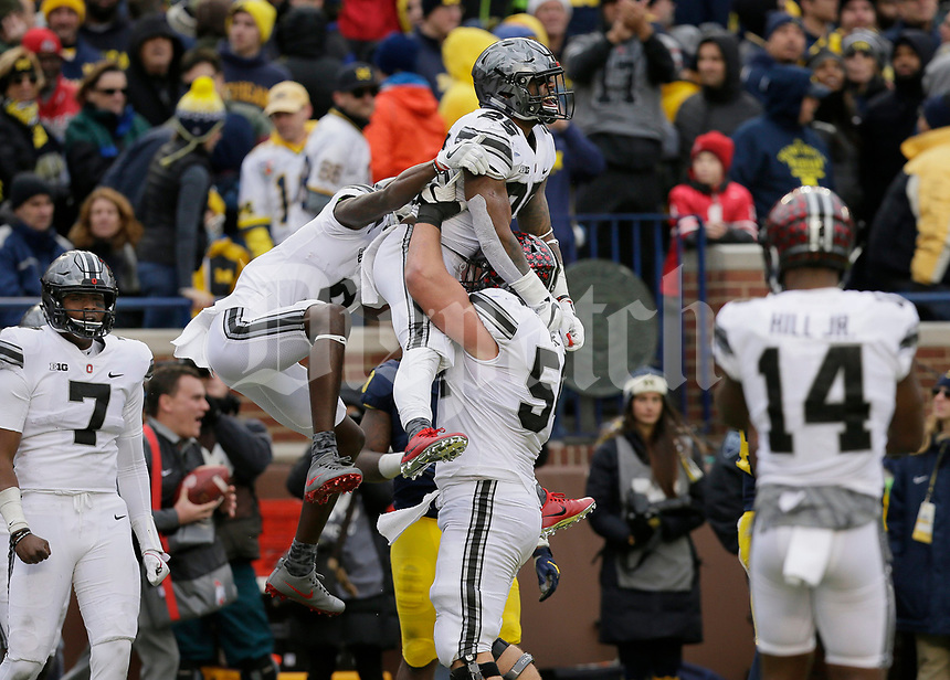 Ohio State Buckeyes offensive lineman Billy Price (54) lifts running back Mike Weber (25) while celebrating with wide receiver Binjimen Victor (9) after he scored a 25-yard touchdown during the fourth quarter of the NCAA football game at Michigan Stadium in Ann Arbor on Nov. 25, 2017. Ohio State won 31-0. [Adam Cairns/Dispatch]