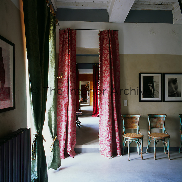 A country room with a beamed ceiling and painted stone walls. Black and white photographs are displayed above antique dining chairs. An open doorway leading to other rooms are flanked by red pattern curtains