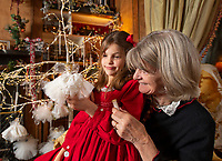 BNPS.co.uk (01202 558833)<br /> Pic: PhilYeomans/BNPS<br /> <br /> Dinah's granddaughter Carla(7) lends a hand...<br /> <br /> Fairy Grandmother - Bespoke fairy maker Dinah Nicholson gets a helping hand from grandchildren Franka, Carla and Daisy this Christmas...<br /> <br /> Described as a 'Living National Treasure' by Country Life magazine her unique creations have even been supplied as wedding gifts for the bridesmaids at Royal weddings.<br /> <br /> Each of her 4159 creations so far have been logged in a fairy ledger, and the £60 cost has never been increased as 'I want everyone to be able to afford one'.