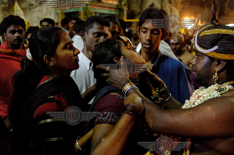 An ethnic Tamil woman is ritually released from her trance-like state by a pilgrim group leader, pushing her forehead, at the ecstatic climax to her pilgrimage to the Batu Caves as part of the annual Thaipusam festival.  The Tamil Hindu festival of penance and thanksgiving commemorates the birth of Hindu Lord Murugan and his triumph over evil. Pilgrims engage in various acts of devotion such as carrying burdens, flagellation and body piercing as they take part in a 15-kilometre procession to the Batu Caves. .