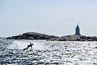 A thrill seeker kiteboards past the Sakonnet Point Light.