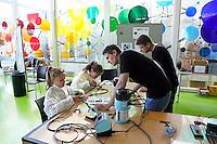 Nederland  Amsterdam  2016. Weekend van de Wetenschap. Open Dag van het Science Park. Workshop signaalvanger solderen bij AMOLF.  Het FOM-instituut AMOLF is een van de onderzoeksinstituten van de Stichting voor Fundamenteel Onderzoek der Materie ( FOM ), en maakt deel uit van de Nederlandse Organisatie voor Wetenschappelijk Onderzoek ( NWO ). AMOLF verricht fundamenteel onderzoek, voor technologische innovaties, op het gebied van Nanofotonica, Moleculaire Biofysica, Systeem Biofysica en Photovoltaics.  Foto Berlinda van Dam / Hollandse Hoogte