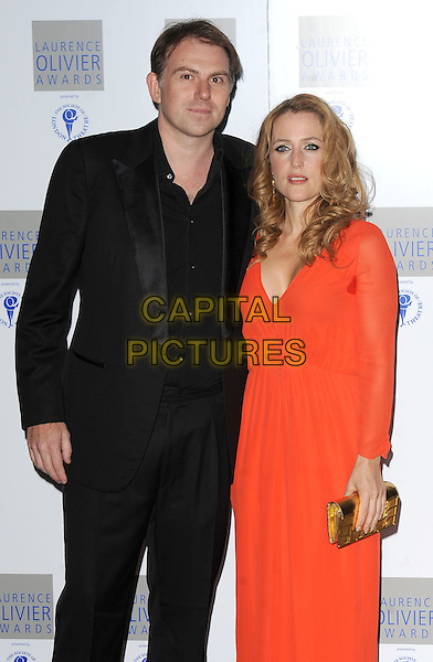 MARK GRIFFITHS & GILLIAN ANDERSON.The Laurence Olivier Awards 2010, Grosvenor House Hotel, London, England..21st March 2010.half 3/4 gold clutch bag length dress red orange sheer look closer circle of shame sweat patch black suit couple .CAP/BEL.©Tom Belcher/Capital Pictures.