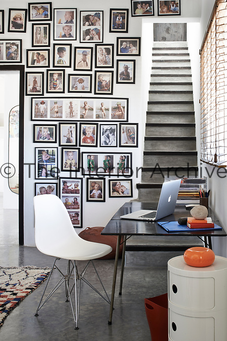 A collection of family photographs adorns a wall in the study, which is simply furnished with a classic Eames chair, a plain desk and round storage caddy.
