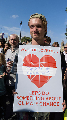 A demonstrator wears a placard which says 'For the Love of Everyone (that's the point!) Let's Do Something About Climate Change' as he marches in front of the Houses of Parliament during the Climate Change demonstration, London, 21st September 2014. © Sue Cunningham