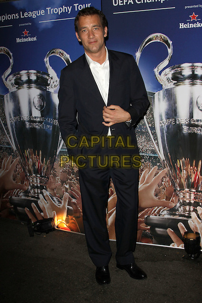CLIVE OWEN.Heineken is Importing The Revered UEFA Champions League Soccer Trophy to America held At Les Deux,  Hollywood, California, USA, .16th March 2010..full length  white shirt tanned sun tan black suit hand in pocket shoes .CAP/ADM/KB.©Kevan Brooks/Admedia/Capital Pictures