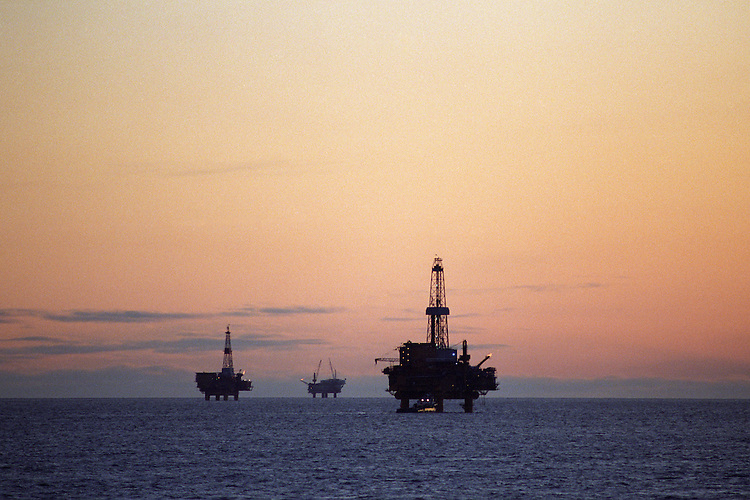 Oil industry platforms stand at sunset in Cook Inlet, offshore from Nikiski, Alaska. Oil and natural gas are an important contributor to the Kenai Peninsula's economy.