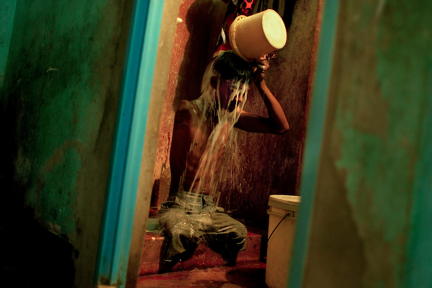 Mohammad Sharif bathes in his house in Chittagong, Bangladesh.