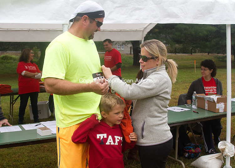 SOUTHBURY, CT.- 21 SEPTEMBER 2014 - 092114JW05. - Peter Linn of Watertown gets prepared to run in Southbury's 25th Annual Fall Classic 10K Road Race with the help of family Uli Linn age 5 and Pilar Santos Sunday morning at Community House Park.<br /> Jonathan Wilcox Republican-American