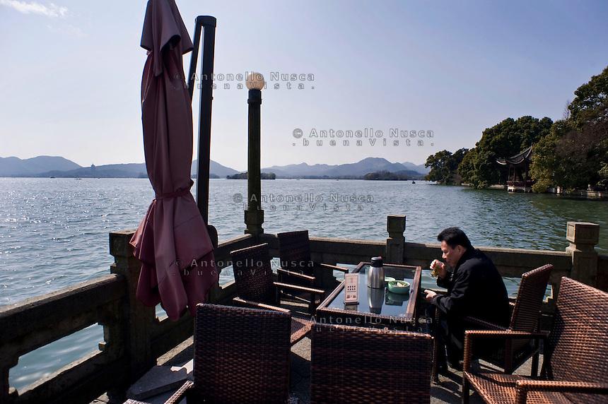 Un uomo beve il suo te in una terrazza del Lago dell'Ovest.<br /> A man drinking tea in a terrace bar at the West Lake in Hangzhou
