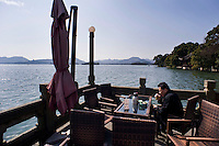 Un uomo beve il suo te in una terrazza del Lago dell'Ovest.<br /> A man drinking tea in a terrace bar at the West Lake in Hangzhou