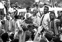 Nelson Mandela holds a child a crowd of ANC supporters April 21, 1994 in Durban, South Africa. The pre-election as he is surrounded by supporters and press at rally is just days before the historic democratic election on April 27, 1994 that Mr. Mandela won. Mr. Mandela became the first black democratic elected president in South Africa. He retired from office after one term in June 1999.