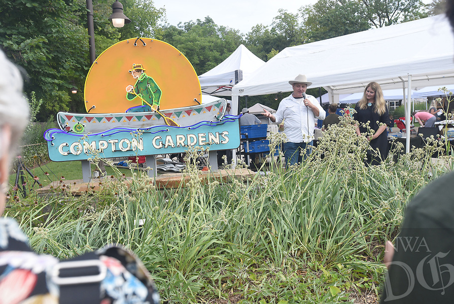 NWA Democrat-Gazette/FLIP PUTTHOFF <br /> HONORING DR. COMPTON<br /> Todd Sanders (left) of Austin, Texas talks to a crowd Saturday Aug. 10 2019 about the neon sign he designed and built that is now part of Compton Gardens in Bentonville. The sign shows the late Dr. Neil Compton, a physician from Bentonville, paddling his aluminum canoe that is festooned with a triangular flag design. Dedication of the sign was part of Dr. Compton Day at Compton Gardens, which featured a variety of conservation activities. Dr. Compton was a founder of the Ozark Society which was instrumental in keeping the Buffalo National River free of dams. He championed  conservation efforts in Arkansas and beyond. His canoe is on display at Compton Gardens two blocks north of the town square. Debra Layton (right), executive director of the Peel Compton Foundation, hears Sanders' remarks.