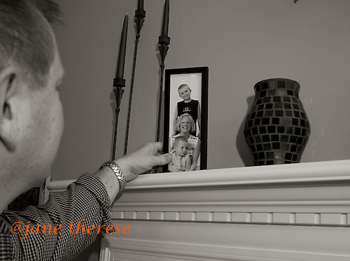 """Stacy takes a moment to look at a photo of his wife Jill, with their two boys, then, Drew 4 and Danny 9. """"Who would've known? Jill wants to sell the house and buy a condo in Haddonfield, that's if both boys are at Bancroft. I'm not there just yet. But I do need to start thinking in that direction."""" photo by jane therese"""