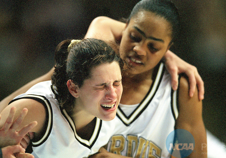 28 MAR 1999: Stephanie White-McCarty (22) of Purdue University gringes in pain after spraining her ankle late in the game as she is helped off the court by her teammate Ukari Figgs (5) during the Division 1 Women's Basketball Championships held at the San Jose Arena in San Jose, CA. Purdue went on to defeat Duke 62-45 for the National Championship. Ryan McKee/NCAA Photos.