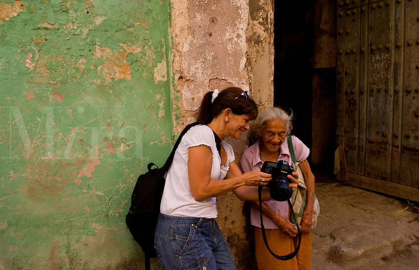 Havana capitol city of Cuba with local old woman portrait and photographer showing digital image in their neighborhood in the city
