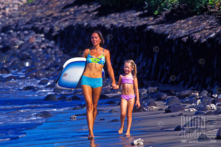 A fit woman carries a bodyboard under her arm and holds the hand of a young girl  as they walk along the shore of a Maui beach.
