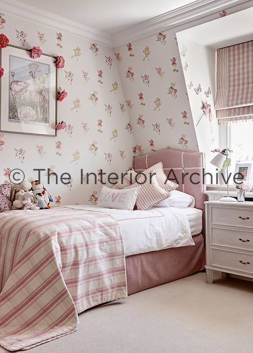 A girl's bedroom decorated with wallpaper with a fairy motifs. A single bed is dressed with furnishings in shades of pink and striped and check patterns.