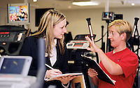 University student (black clothes) on a work placement in a London hotel's gym.