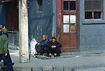 Older Men Sitting On Sidewalk