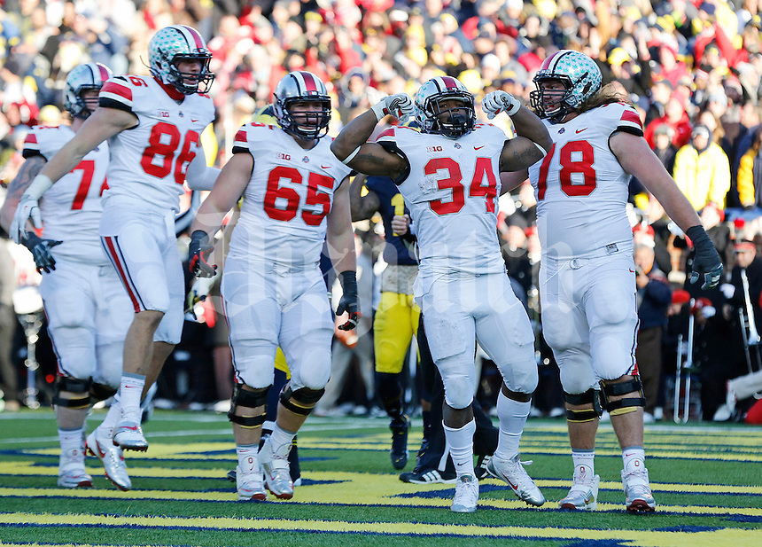 Ohio State Buckeyes running back Carlos Hyde (34) flexes after scoring the team's final touchdown in the fourth quarter of the college football game between the Ohio State Buckeyes and the Michigan Wolverines at Michigan Stadium in Ann Arbor, Michigan, Saturday afternoon, November 30, 2013. The Ohio State Buckeyes defeated the Michigan Wolverines 42 - 41. (The Columbus Dispatch / Eamon Queeney)