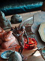 On the living room table sits a bronze statue of a snake charmer by the nineteenth century French artist Arthur Bourgeois. Next to it sits an Ottoman incense burner, and a shell-shaped nineteenth century porcelain bowl
