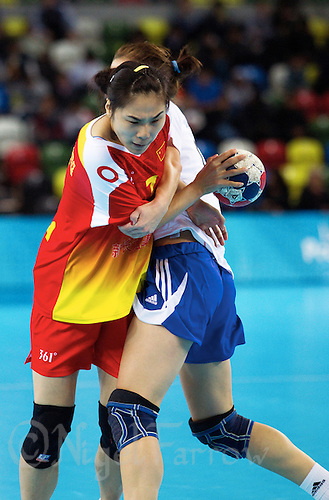 23 NOV 2011 - LONDON, GBR - China's Luan Zheng (in red and yellow) tries to get past Slovakia's Martina Kosikova (in white and blue) during their 2011 London Handball Cup match at The Handball Arena in the Olympic Park in Stratford, London .(PHOTO (C) NIGEL FARROW)