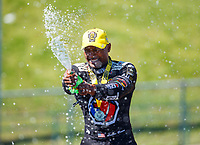 May 21, 2017; Topeka, KS, USA; NHRA top fuel driver Antron Brown celebrates by spraying Mello Yello soda after winning the Heartland Nationals at Heartland Park Topeka. Mandatory Credit: Mark J. Rebilas-USA TODAY Sports