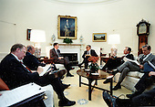 United States President Ronald Reagan meets with Dr. Henry Kissinger, Chairman of the National Bipartisan Commission on Central America, in the Oval Office of the White House in Washington, DC on January 6, 1983.  Also present at the meeting are (clockwise from left): Edwin Meese, Counsellor to the President; US Secretary of State George Shultz; Vice President George H.W. Bush; and James A. Baker III, Chief of Staff and Assistant to the President.<br /> Mandatory Credit: Jack Kightlinger / White House via CNP