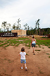 Amanda Porter and her daughter Krista Holbrooks, 5, walk on her father's property near where her house is being rebuilt after an April tornado tore apart the community and destroyed both homes on the property.
