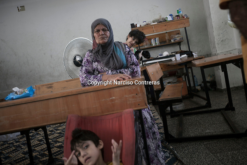 """In this Saturday, Aug. 16, 2014 photo, Mahmod (front), a 14 yo teenager who is mental disable, Malak (back), a 13 yo who is mental disable, and their grandmother (middle), are seen inside a classroom at the Al-Zaytoon UN School turned into a temporary refugee after their family fled from Shuyaja neighborhood when the IDF targeted and destroyed their house during the """"Protective Edge"""" military operation in Gaza Strip. Mahmod and Malak are two of four mental disable brothers and sisters of the father Jawal's family (not pictured).  (Photo/Narciso Contreras)"""