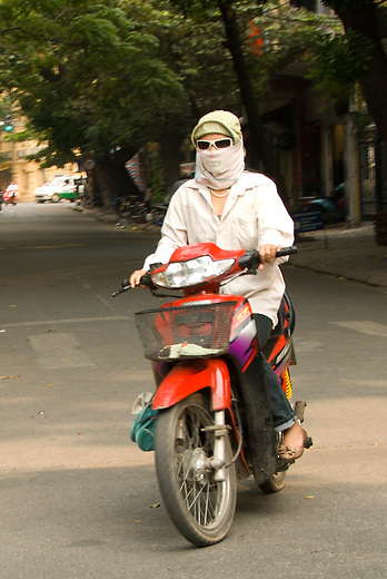 A girl on a motorbike in Hanoi, Vietnam. Many Vietnamese wear face shields to protect themselves from the motorbike and car fumes. Emissions are  unregulated and produce a significant amount of air pollution in the cities.