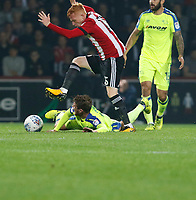 Andreas Weimann of Derby County is hurdled by Ryan Woods of Brentford during the Sky Bet Championship match between Brentford and Derby County at Griffin Park, London, England on 26 September 2017. Photo by Carlton Myrie / PRiME Media Images.