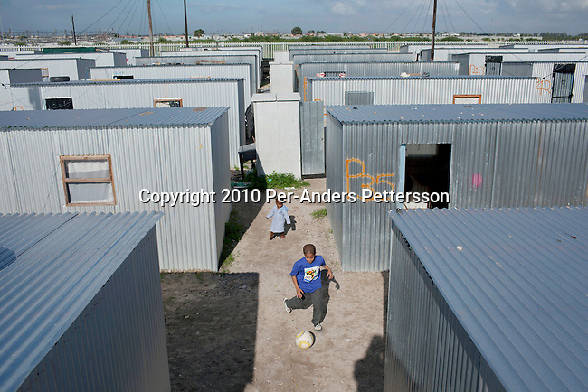 "CAPE TOWN, SOUTH AFRICA - MAY 3: An unidentified boy practice soccer between tin shacks on May 3, 2010, in Blikkiesdorp about 40 kilometers south of Cape Town, South Africa. Blikkiesdorp, which is Afrikaans for ""Tin Can Town"", was given its name by its residents because of the row-upon-row of tin-like shacks made of corrugated iron. It was built by the City of Cape Town in 1997 and about 1600 one-roomed shacks were built. It has been known for its bad conditions and a dumping ground for shack dwellers from other areas around Cape Town. Recently many street people in Cape Town has been forcefully removed and relocated to this place. The ones that have refused has been put in holdings cells or prisons such as Pollsmoor Prison. This campaign has  identified in the preparation for the soccer World Cup, who starts on June 11, 2010 and goes on for a month. The City of Cape Town doesn't want international visitors to be hassled by street people. (Photo by Per-Anders Pettersson)"