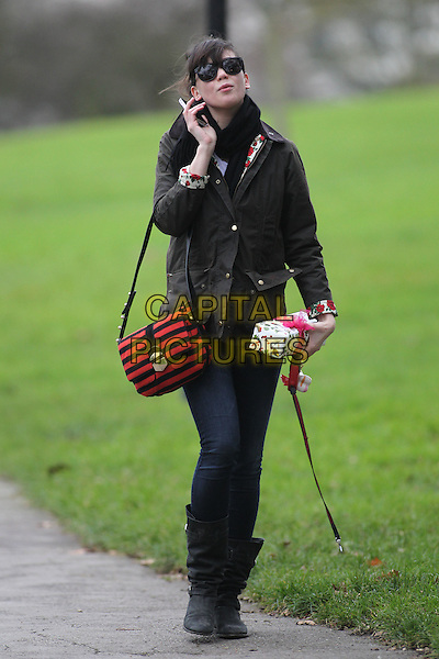 Daisy Lowe .walking and talking on her mobile phone in Primrose Hill, London, England..28th December 2011.full length black jacket jeans denim boots red striped stripes satchel bag sunglasses shades phone scarf white floral print box gift present .CAP/HIL.©John Hillcoat/Capital Pictures.