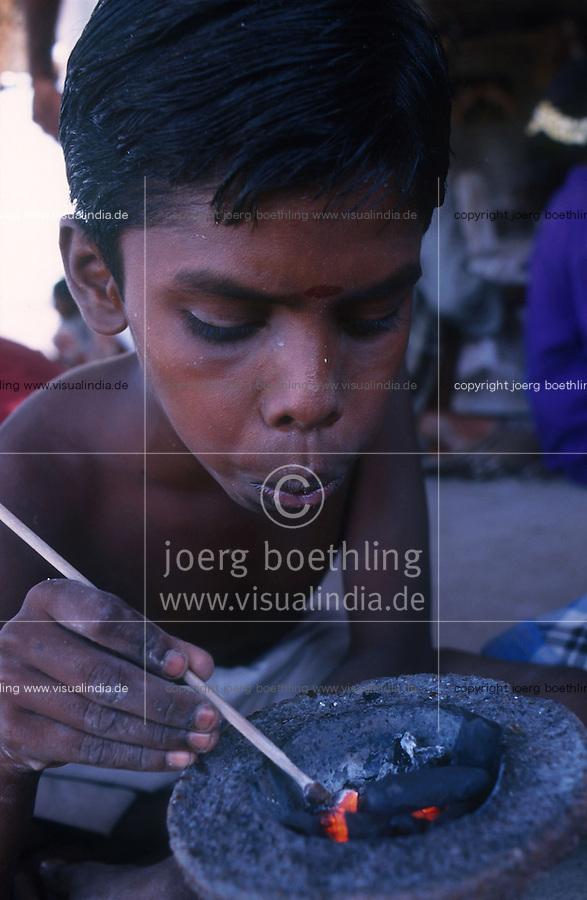 INDIA Tamil Nadu, Karur, child labour, boy work in a polishing unit for artificial synthetic gems, he is putting the stones on bamboo sticks with wax before polishing / INDIEN, Kinderarbeit, Junge arbeitet in einer kleinen Edelsteinschleiferei im Dorf V. Pudur bei Karur, hier werden Halbedelsteine und kuenstliche Edelsteine poliert