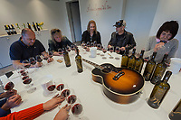Switzerland. Canton Ticino. Cagiallo. Merlot wine testing for the new Magnificents' 17. Sacha Pelossi (L), the Gotthard musicians Leo Leoni (LC), Nic Maeder (C), Freddy Scherer (CR), Valentina Andrei (R). On the table, among wine bottles and glasses, a guitar Gibson Super Jumbo, SJ-200, belonging to Leo Leoni. The Swiss rock band Gotthard is associated with winemakers Valentina Andrei (Merlot Ivresse from Valais) and Sacha Pelossi (Merlot from Ticino) to create the new assemblage (50-50 from both winemakers) for a unique vintage bottle: Magnificents' 17. Gotthard is a Swiss hard rock band founded in Lugano by Steve Lee and Leo Leoni. Their last eleven albums have all reached number 1 in the Swiss album charts, making them one of the most successful Swiss acts ever. With 2 million albums sold, they managed to get multi-platinum awards in different parts of the world. Cagiallo is a village and and is part of the Capriasca municipality. 25.03.2019 © 2019 Didier Ruef