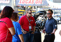 Apr 11, 2015; Las Vegas, NV, USA; NHRA top fuel driver Steve Torrence (right) gives a tour to VIPs during qualifying for the Summitracing.com Nationals at The Strip at Las Vegas Motor Speedway. Mandatory Credit: Mark J. Rebilas-